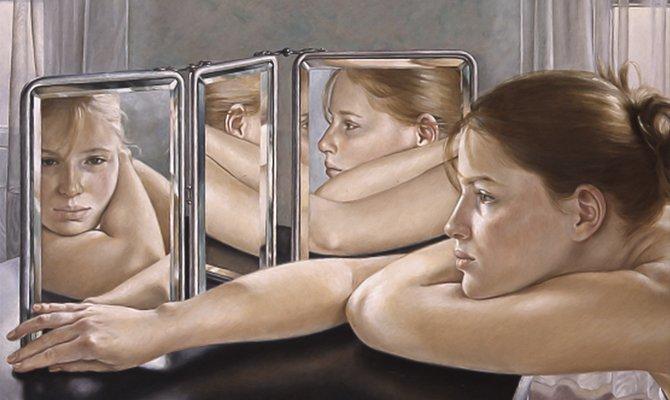 Девушка сидит в печали перед зеркалом