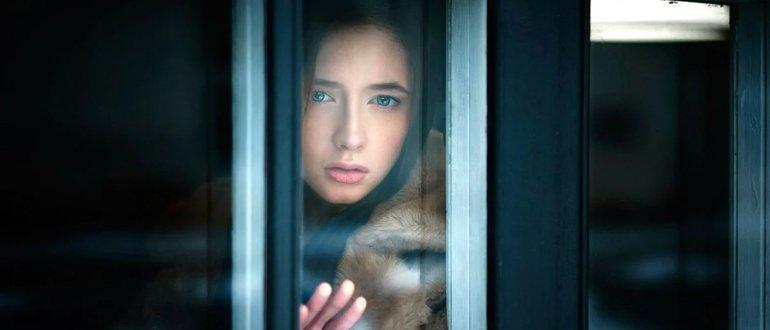Девушка смотрит из окна