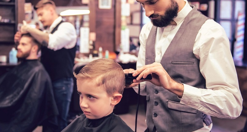 Стригут мальчика в парикмахерской